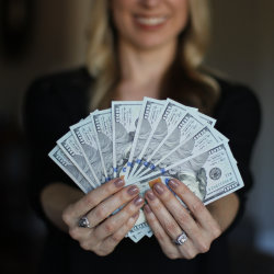 woman holding $1000 in cash